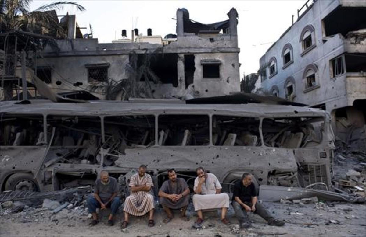 Cinco palestinos de Gaza sentados frente a un autobús y un edificio destruidos, en el 2014, por ataques aéreos israelís. AFP/ROBERT SCHMIDT